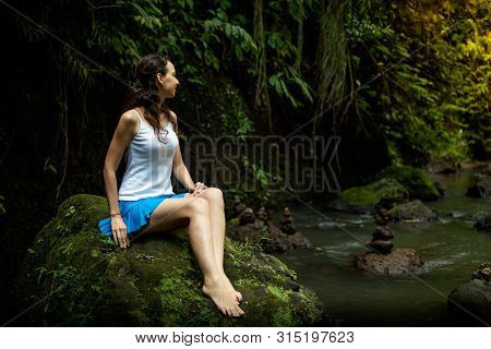 Young Caucasian Woman Sitting On The Rock, Enjoying River View Near Waterfall. Vacation In Asia. Cal