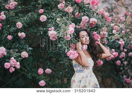 Young Beautiful Woman With Long Healthy Curly Hair Wearing Pink Vintage Dress And Posing In Garden W