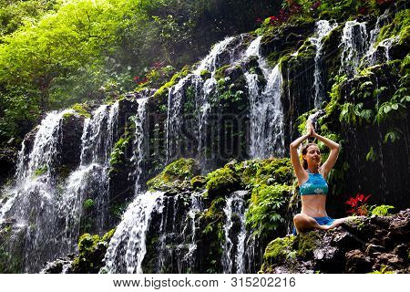 Healthy life. Yoga retreat. Young Caucasian woman sitting on the rock, meditating, practicing yoga, pranayama with namaste mudra at waterfall. Banyu Wana Amertha waterfall Wanagiri, Bali.