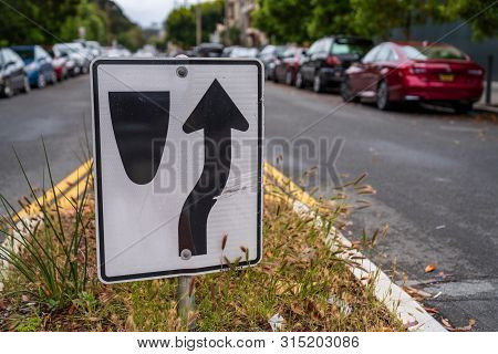 Traffic Sign Directing Cars To Go To Right Of Median Along A Crowded Street