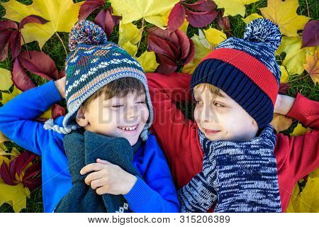 Two Little Brother Kids Boys Lying In Autumn Leaves In Colorful Casual Clothing. Happy Siblings Havi