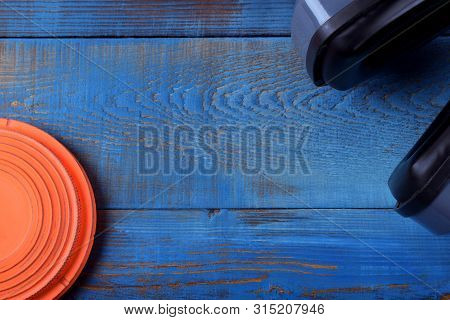 Flying Target Plate And Noise Suppression Headphones Against The Blue Wooden Background. Copy Space
