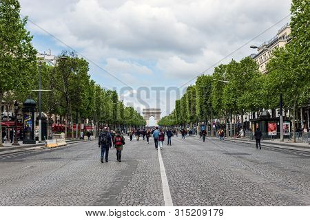 Paris, France - May 5, 2019: People Wandering On Champs Elysees Avenue With Arc De Triomphe In Backg