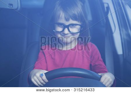Driving Shool. Humorous Portrait Of Cute Little Child Girl Learns To Drive.