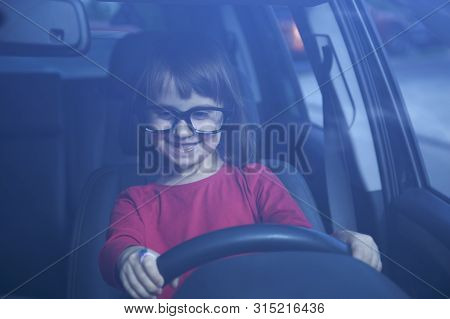 Driving Shool. Humorous Portrait Of Cute Little Child Girl Learns To Drive. Horizontal Photo.
