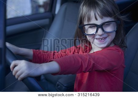 Driving Shool. Humorous Photo Of Happy Cute Little Child Girl Learns To Drive.