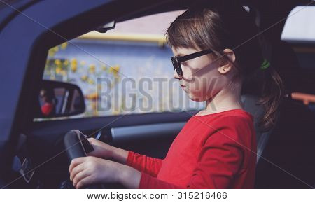 Driving Shool. Humorous Photo Of Cute Little Child Girl Holds A Wheel In A Car And Learns To Drive.