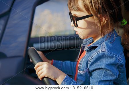 Driving Shool. Humorous Photo Of Beautiful Child Girl Learns To Drive.