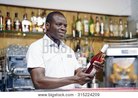African Elderly Bartender Is Holding A Bottle Of Red Wine. The Bartender Examines A Bottle Of Red Wi