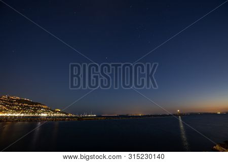 Long Exposure Night Shot Of The Sky Over The Calm Sea With Town Lights And Stars