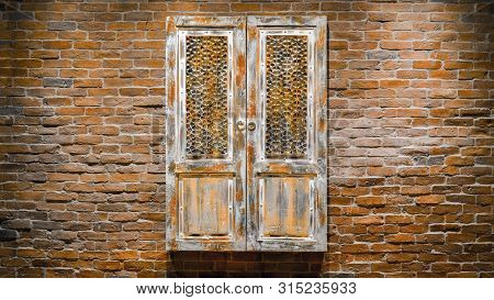 Old Faded Red Wooden Doors With Brick Wall. Old Wooden Door On Brick Wall. Vintage Background. Old I