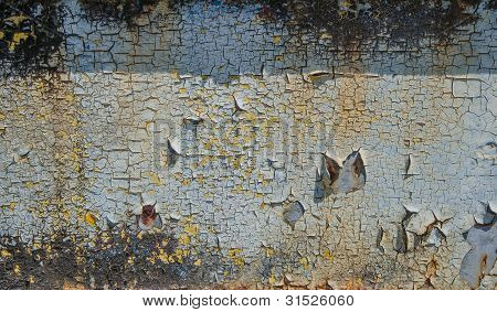 Paint peeling on the side of a rusted piece of metal