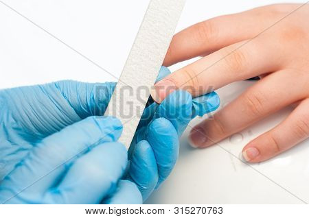 Closeup Shot Of A Woman In A Nail Salon Receiving A Manicure By A Beautician With Nail File. Woman G