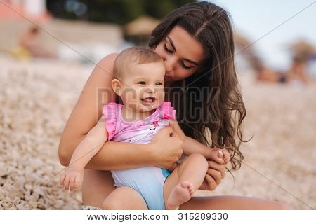 Portrait Of Cute Baby Girl With Her Mother On The Beach. Mom With Daughter In Swimsuit By The Sea. H
