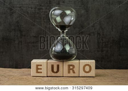 Euro countdown after Brexit referendum to withdraw from Europe, hourglass or sandglass on wooden cube block with alphabet building the word Euro on wood table, dark black background. poster