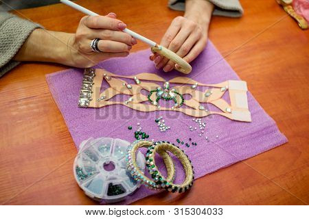 Close-up woman`s hands, decorating bracelets with colorful shiny rhinestones, gluing crystals on a textile base with wax pencil. Handicraft process concept. poster