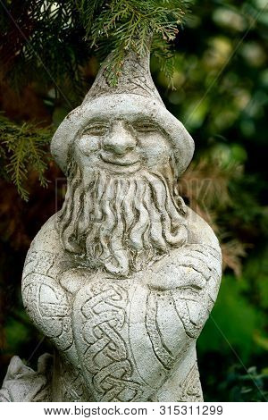 Berlin, Germany - May 04, 2019: Garden Statue Of A Magician With A Pointy Head And Long Beard