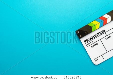 White Acrylic Clapboard Over Turquoise Blue Background. Top View Of Clapboard With Copy Space. Flat