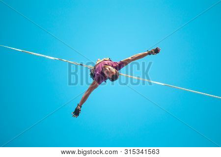 Highliner Hanging From The Blue Sky View From Below. A Man Goes On A Stretched Sling. The Fall Of Th
