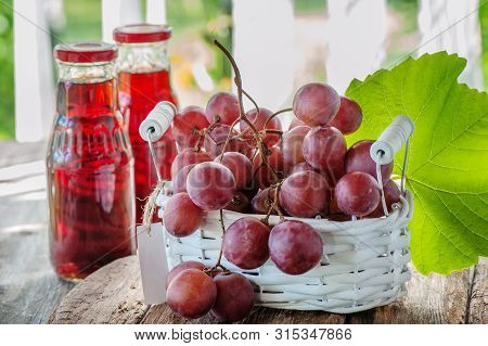 A Bunch Of Pink Grapes, Prepared To Extract The Juice, Is In A White Basket . Two Bottles Of Grape J