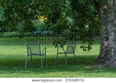 Tranquil Scene With Two Chairs On A Green Lawn In A Park Under A Hugh Tree On A Sunny Day