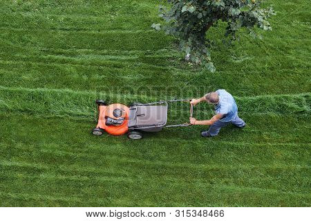 Man Cuts The Lawn. Lawn Mowing. Aerial View Lawn Mower On Green Grass. Lawn Mower Mower. Mowing Tool