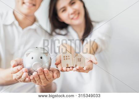 Cropped Shot Of Happy Asian Couple Holding Piggy Bank And Wooden House Models. Saving Money For Buyi