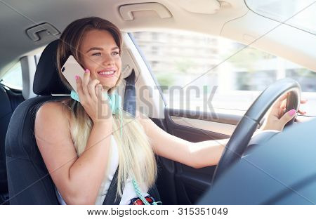 Young Woman Talking On A Cellphone While Driving A Car. Cell Phones And Driving Do Not Mix Well For