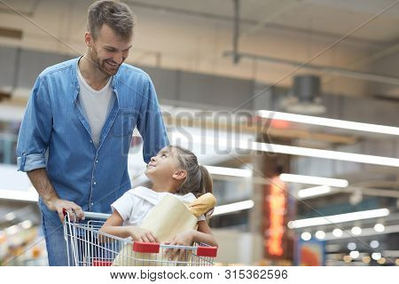 Portrait Of Happy Young Father Grocery Shopping In Supermarket And Smiling At Little Girl Sitting In