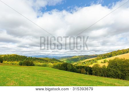 Beautiful Countryside In Mountain. Trees On Grassy Hills. Sunny September Weather With Cloudy Sky. W