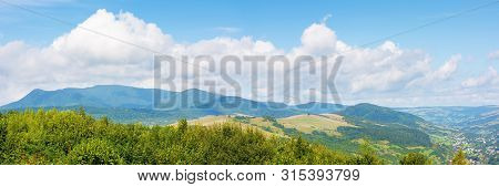 Beautiful Countryside In Mountain. Sunny Weather. Clouds On The Blue Sky. Lovely Panoramic Landscape