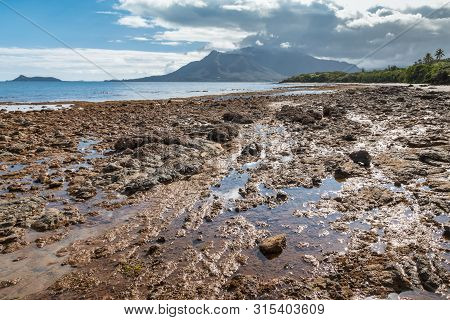 Rocky Beach Near Plum In New Caledonia With Mont-dore Mountain At Low Tide