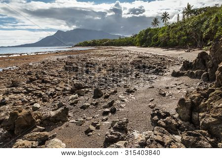 Rocky Beach Near Plum On New Caledonia Coast With Mont Dore Mountain In Background