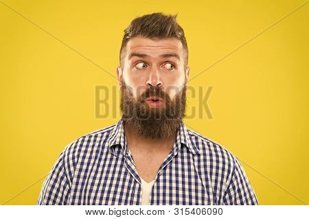 Man Bearded Hipster Wondering Face Yellow Background Close Up. Guy Surprised Face Expression. Hipste