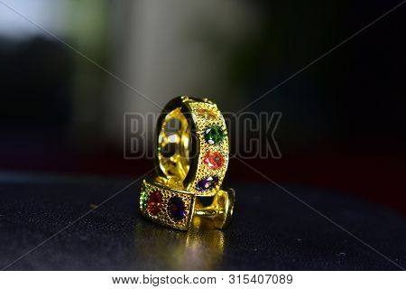 Gold earrings Adorned with 4 precious stones, 4 beautiful colors and expensive poster