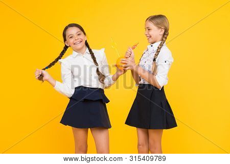 Say yes to health. Small schoolchildren drinking juice from orange fruits for their health on yellow background. Nutrition for kids health. Drinking juice can boost your health. poster