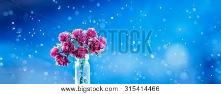Colourful Flying Magical Bokeh Above Pink Rose Flowers And Blur Soft Focus Blue Background. Abstract