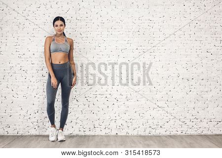 Sport Woman In Sportswear Relax Stand After Workout Against Copy Space For Adding Text With White Wa