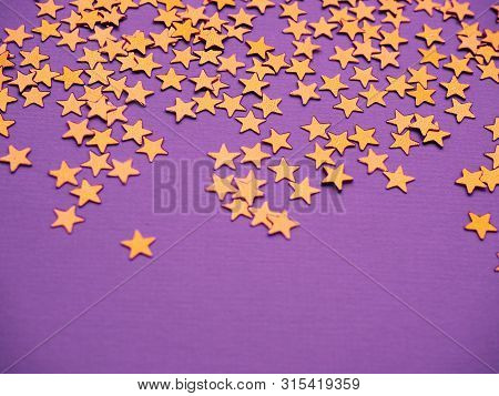 Golden Stars Glitter On Lavender Paper Background. Festive Holiday Bright Backdrop