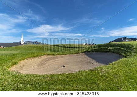 Golf course with sand bunker and vibrant fairway under blue sky on a sunny day poster