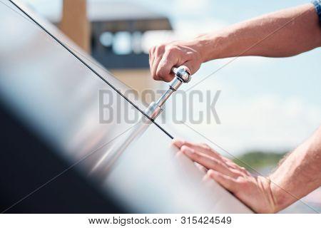Hand of technician master turning steel handle or worktool