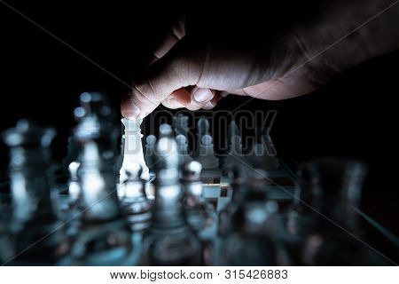 The Concept Of Business Competition: Close-up Of A Businessman Holding A Glass Chess