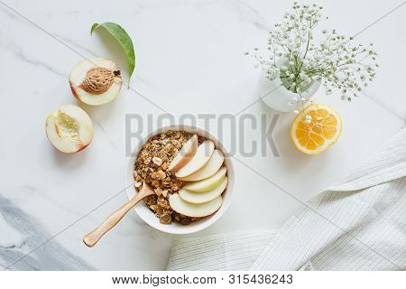 Bowl Of Granola With Nectarine Fruit On Marble White Table