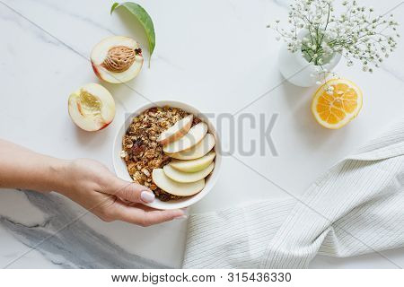 Bowl Of Granola With Nectarine Fruit On Marble White Table.