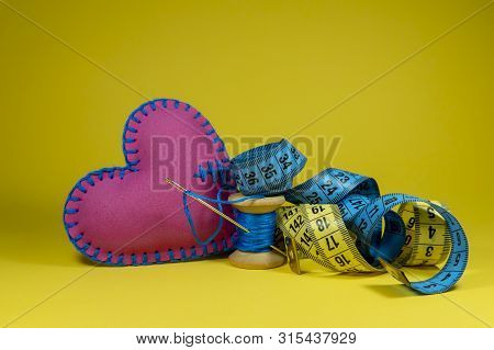 Hand Stitched Fabric Heart, Tape Measure And Spool Of Thread With Needle On Yellow Background, Handm