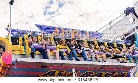Sarina, Queensland, Australia - August 2019: People Holding Tight In A High And Fast Thrill Ride At