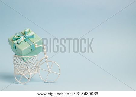 A Toy Bike Carries A Gift. The Idea For A Postcard. Blue Background. Minimalism