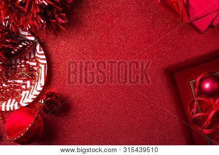 Merry Christmas And Happy New Year Red Background.top View Of Tinsel,gift Box,ball,ribbon Decorate O