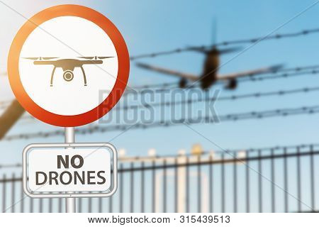 Close-up Of Drone Prohobition Sign Against Security Fence And Airplane Landing On Airport