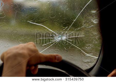 Broken Windshield Of A Car. A Web Of Radial Splits, Cracks On The Triplex Windshield. Broken Car Win